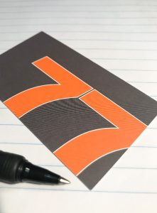Is your marketing working. Image of the orange and grey 77 Design co business card on white paper with a pen.