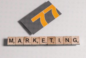 Marketing success stories. Marketing Scrabble tiles and a 77 Design Co business card.