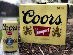 A photograph of a case of Coors Original Banquet beer outdoors.