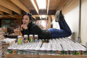 Interview-Sobel's Obscure Brewery. Jackie Sobel laying on a case of beer in a black sweater and jeans.