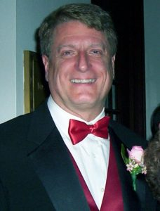 DJ Little Larry Joe in a black tuxedo and red bow tie at an event.