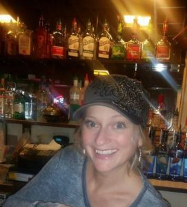 Photograph of Dee Bertison bartending with a dark gray hat and sweater on.