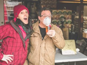 Interview-Sobel's Obscure Brewery. Jackie Sobel in a red tossle cap and red coat. David Sobel in a tan jacket with a beer wearing a mask to protect for Coronavirus.