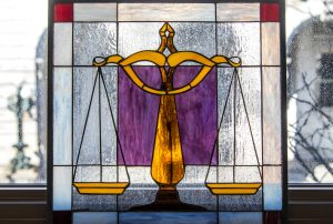 Interview-Attorney William J. McCabe. Criminal defense law. Image of purple and orange stained glass scales of justice.
