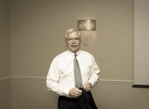 IInterview-Attorney William J. McCabe. Criminal defense law. Photograph of Dr. Bill McCabe in white dress shirt with gray tie.