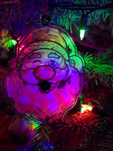 Image of a green and red Santa Clause Christmas Tree ornament. Holidays in 2020.